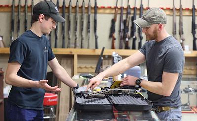 Tyler Kabay (left) shows an AR-15 to Rob Kenny of Butler at Fenelton Firearms in Fenelton Thursday. Seb Foltz/Butler Eagle 03/11/21