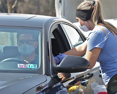 UPMC staff member Taylor Bajus gives a vaccination shot to Chris Karg of McCandles at the UPMC Lemieux Sports Complex drive-thru vaccination Wednesday. Seb Foltz/Butler Eagle 03/17/21
