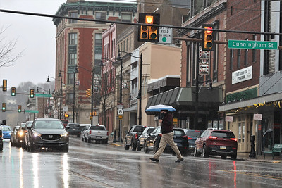 A pedestrian crosses Main St. at the intersection with Cunningham St. Thursday afternoon. Dreary skies brought significant rainfal to the region, making for a wet evening commute. Seb Foltz/Butler Eagle 03/18/21