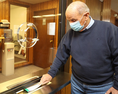 Franklin Township supervisor Bob Thompson demonstrates sliding a paper under the clerk window at the municipal building. The township purchased the bulletproof glass window with CARES Act funds. Seb Foltz/Butler Eagle 03/10/21