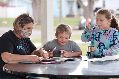 Butler Area School District instructional coach Karen Robb reads to Reece Floyd,6,(center) and Austin Schmeider,9, during a meet-and-greet and Bookstop book pickup with new Broad Street Elementary principal Vanessa Boyd (not pictured). The elementary school will reopen this fall. Seb Foltz/Butler Eagle 03/23/21