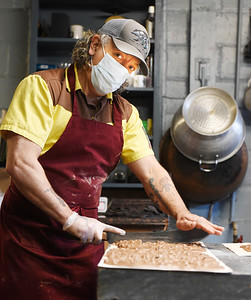 Third-generation, candy maker Barry Cummings cuts chocolate espresso bars Thursday, March 25, 2021. According to Cummings, his family has been making candy at 146 N. Main St., Butler since 1905. Harold Aughton/Butler Eagle