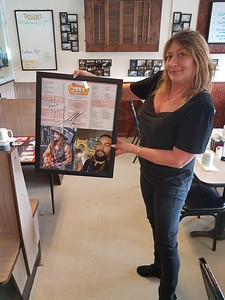 Jacqueline Miller, the owner of Roxy's Diner in Prospect, holds a menu and signed photographs of actor Jason Momoa who filmed a scene in the diner in December 2019. EAGLE PHOTO BY ERIC FREEHLING