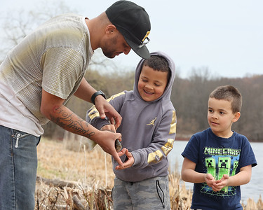 Alco Lyles, 42, shows his sons Julian, 7, (center) and A.J. Lyle,6, how to hold a bluegill at Moraine State Park Saturday. According to the Pennsylvania Fish and Boat Commission, the first Saturday before trout season is  Mentored Youth Trout Fishing Day, a day where children can fish without a license under the supervision of a licensed adult. Seb Foltz/Butler Eagle 03/27/20