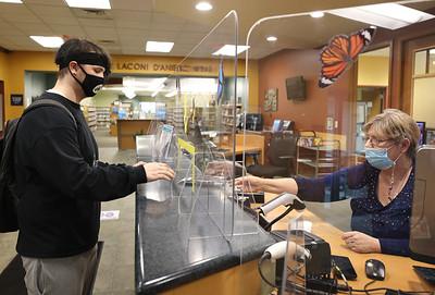 Bradey Duncan checks out a book from Alice Baptiste at the Butler Library Tuesday. Seb Foltz/Butler Eagle 05/04/21