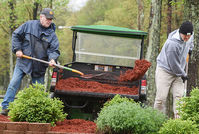 The rain didn't deter maintenance workers Rob Mitchell, left and Terry Davis from spreading mulch at Alameda Park Wednesday. Harold Aughton/Butler Eagle.