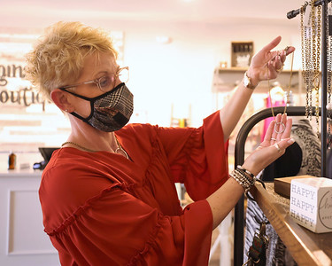 Mainstream Boutique owner Christine Dunn picks out a necklace from her store's accessory section. Seb Foltz/Butler Eagle 04/21/21