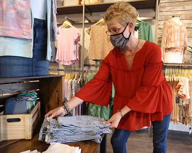 Mainstream Boutique owner Christine Dunn refolds a pants display in her Cranberry store. Seb Foltz/Butler Eagle 04/21/21