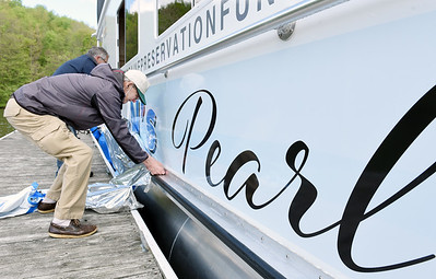 Senior captain, William Moutz and board member Andy Piccuta of the Moraine Preservation Fund, unveils the name of the organization's new pontoon boat, Preston's Pearl during a ceremony at Lake Arthur, Thursday. Harold Aughton/Butler Eagle.