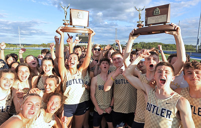 Butler's Ali Altman and Jordan Stutz raise the girls and boys WPIAL team championship trophies Wednesday with teammates following the meet in West Mifflin. Seb Foltz/Butler Eagle 05/12/21