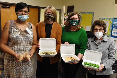 From left, Charlene Large, parent, Robin Stuchell, guidance secretary, April Christy, school psychologist, and Roberta Fox, substitute teacher at Karns City High School display one of the many meals being distributed to children through the United Way. Harold Aughton/Butler Eagle.