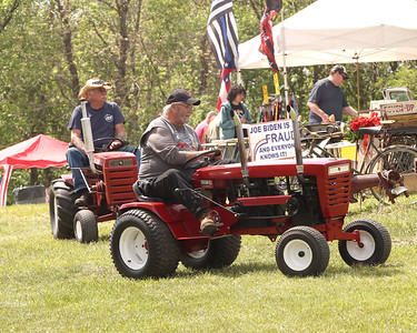 Daryl Dickey (front) and Bill Kwolek cruise through the flea market section of the Portersville Steam Show on their classic model and modified Wheel Horse tractors Saturday. Seb Foltz/Butler Eagle 05/15/21
