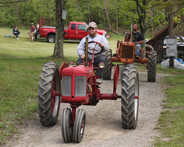 Jeremy Hamilton of Portersville drives his 1949 Farmall C through the Portersville Steam Show Grounds Saturday with Kevin Weibel of Harmony(back). Seb Foltz/Butler Eagle 05/15/21