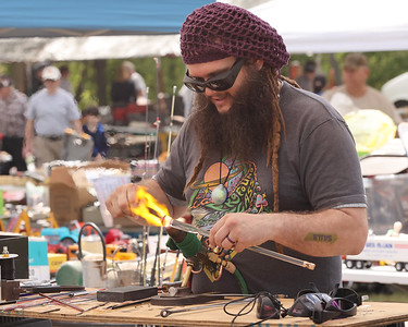 John Cooney, 34, of Slippery Rock demonstrates his glass blowing technicque at his booth at the Portersville Steam Show Saturday. Seb Foltz/Butler Eagle 05/15/21
