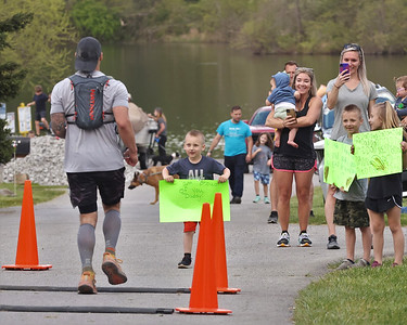 Luca Rosenfeld, 3, holds up a sign for his father Eddie Rosenfeld at the finish of the Glacier Ridge Trail Ultramarathon & Trail Race Saturday at Moraine State Park. Rosenfeld ran the 50-mile race. The annual event also includes 30 and 50 kilometer courses.