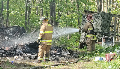 EDDIE TRIZZINO/BUTLER EAGLEA fire crew from Herman Volunteer Fire Company extinguishes flames from a trash fire at 3550 Beck Road Monday afternoon.