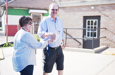 Toni Grupp, 70, of Butler hands a pamphlet about Common Pleass judicial candidate Joe Kubit to Pete Szura, 70 of Butler, as he enters Butler City Precinct 5 on May 18, 2021 to vote in the primary election. For the primary election, this precinct was located at the Salvation Army on Cunningham Street.  Lauryn Halahurich/Butler Eagle