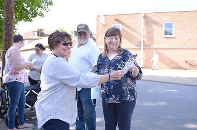 Toni Grupp, 70, of Butler hands a pamphlet about Common Pleas Judge candidate Joe Kubit to to Holly Hartzell, 64, of  Butler outside the  Butler City Precinct 5 on May 18, 2021. Standing behind Holly is Tom Hartzel, 65, of Butler.  For the primary election, this precinct was located at the Salvation Army on Cunningham Street.  Lauryn Halahurich/Butler Eagle