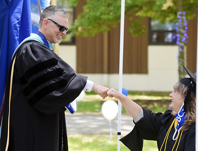 BC3 president Nicholas Neupauer fist bumps Sherri Mack, dean of business prior to the graduation ceremony Wednesday afternoon. Harold Aughton/Butler Eagle.
