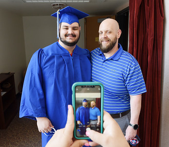 Rachel Klumph takes a photo of her stepson, Kyle Klumph with his father Todd Klumph of West Middlesex prior to the BC3 graduation ceremony. Kyle earned an associate's degree in business administration. Harold Aughton/Butler Eagle