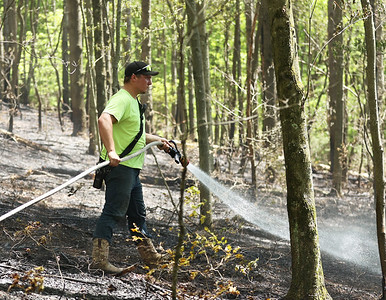A firefighter sprays down a brush fire that started near the train tracks along Chicora Road on May 20, 2021. Photo by Seb Foltz/Butler Eagle