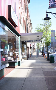 Pictured on May 20, 2021 with partially empty storefront windows is Miller's Shoes, located at 215 South Main Street in Butler. The store has been closed since January after a fire damaged three of the neighboring buildings.   Owner of Miller's Shoes, Jimmy Chiprean, said the 129-year-old store will see a grand re-opening event in mid- to late July. The heavy smoke from the fire didn't damage Chiprean's stock, but caused a smoky smell that rendered many shoes, boots, clothing and accessories unsalable.  Photo by Lauryn Halahurich/Butler Eagle