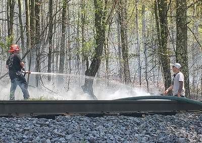 EDDIE TRIZZINO/BUTLER EAGLEFire fighters with Chicora Community Fire Department extinguish flames near train tracks by the Goosetown boundary Thursday afternoon.
