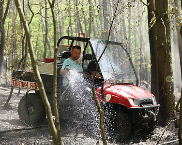 A firefighter in a UTV sprays down a brush fire that started near the train tracks along Chicora Road on May 20, 2021. Photo by Seb Foltz/Butler Eagle