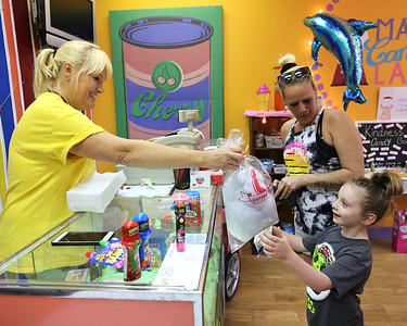 Mars  Candy Land owner Pammie Vivirito gives Nevaeh Moakley, 6, her cotton candy Friday at her Mars store. Seb Foltz/Butler Eagle 05/21/21