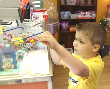 Lee Glover, 4, of Mars puts his candy on the counter at Mars Candy Land Friday. Seb Foltz/Butler Eagle 05/21/21
