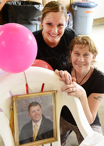 Terry Becker, left, and Brittney Gunther met for the first time at a celebration of life party for Terry's son, Corey Becker, (framed high school picture) who died early this year of COVID-19. Gunther, an EMT, kept Terry informed of Corey's condition while in the hospital. Harold Aughton/Butler Eagle
