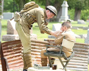 Gus Workman, 12, plays an injured World War I soldier with Vincent Workman,16, tending to him during the Butler County  Historical Society Echoes From Our Past series Saturday at North Side Cemetery. Actors portrayed figures from Butler's past  and recreated scenes their respective eras.  Seb Foltz/Butler Eagle 05/22/21