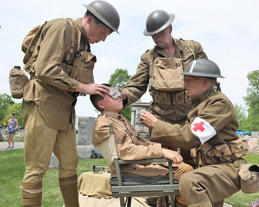 Vincent(left), Gus and Kieth Workman recreate a World War I scene with Paul Sutliff (back), during Saturday's Butler County Historical Society Echoes from our Past series at North Side Cemetery.Sutliff portrayed Richard 'Mad Man' Muntz, a World War I veteran from Butler. Seb Foltz/Butler Eagle 05/22/21