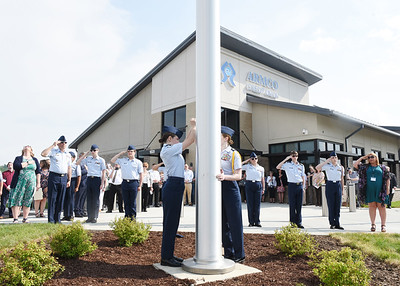 Members of the Mars and Pine-Richland Air Force JROTC cadets led by chief Mike Gasparetto US Air Force (Ret) and Armco mortgage operations supervisor, Mandy Eckstein (US Army Veteran) salute as they raise the American flag up a 70 foot flag pole in front of the new Armco Credit Union Mars Branch located at the intersection of Myoma Rd. and Route 228 Tuesday afternoon. Harold Aughton/Butler Eagle.