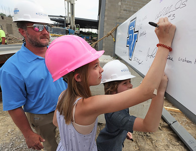 Seneca Valley Area School District Student's Crosby (9) and Lila (11) Fulkerson sign a the final steel beam to be placed in Ehrman Crest Elementary and Ehrman Crest Middle Schools with Brian Fulkerson during the district's topping ceremony Tuesday. Brian Fulkerson is the owners representative for the project. Crosby will attend the school as a fifth grader when it opens in 2022. Seb Foltz/Butler Eagle 05/25/21