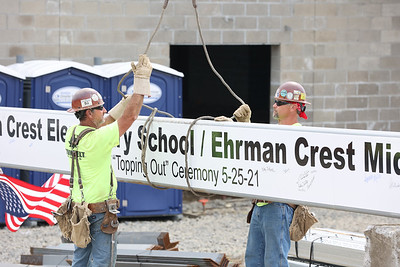 Construction crews raise the final steel beam to be placed in Ehrman Crest Elementary School and Ehrman Crest Middle School  during the Seneca Valley Area School District's topping off ceremony Tuesday.  District officials, school board memebers, students and invited guests signed the beam before construction crews raised and placed the beam. Seb Foltz/Butler Eagle 05/25/21