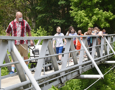 Butler Intermediate teacher Dave McCool leads a group of fifth graders across the bridge on the way to release the trout the classed raised into the Connoquenessing Creek. Harold Aughton/Butler Eagle