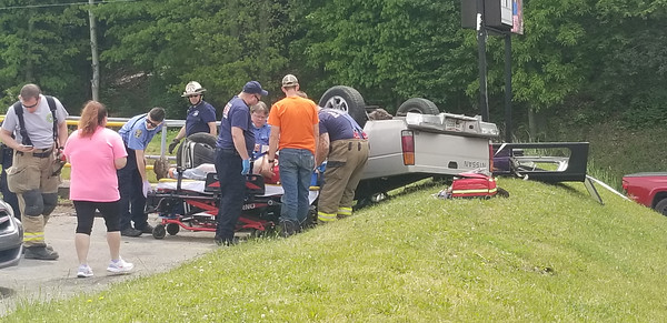 A man driving a 1997 Nissan pickup hit the Family Bowlaway sign, flipped over, and landed on his roof. A witness whose husband was a passenger in the truck said the brakes were faulty. The driver was taken by ambulance for medical treatment.