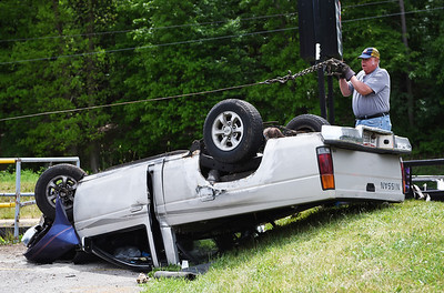 Chuck Himes of Atwell Towing Service attaches a chain to a 1997 Nissan pickup truck that hit the Family Bowlaway sign in Butler Township , flipped over, and landed on its roof on Thursday, May 27, 2021. A witness whose husband was a passenger in the truck said the brakes were faulty. The driver was taken by ambulance for medical treatment.  Lauryn Halahurich/Butler Eagle
