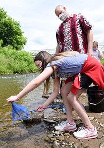 Butler Intermediate teacher Dave McCool watches as fifth grader Makenzie Clark releases trout into the Connoquenessing Creek Thursday afternoon. Harold Aughton/Butler Eagle