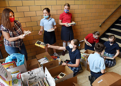Butler Catholic teacher Jessica Friel helps students sort through the over 1600 books collected during a book drive to place books inside the little free library outside the school.  Harold Aughton/Butler Eagle.
