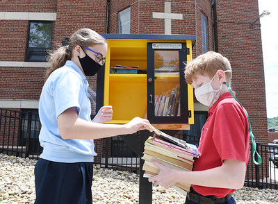 Fifth graders Grace Wolfrum and Cameron Smith fill the Little Free Library with used books outside of Butler Catholic Thursday afternoon. May 27, 2021.  Harold Aughton/Butler Eagle