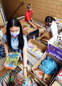 Fifth graders Leah Chau, left, Drew Weifenbaugh and Leslie Best sort books as part of Butler Catholic's book drive Thursday afternoon. Harold Aughton/Butler Eagle