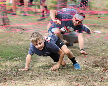 Sebastian Osche, 9, of Butler pulls ahead of his father Seth Osche in the string maze obstacle in Saturday's Tuff Tornado Run at Alemeda Park. Seb Foltz/Butler Eagle 10/02/21