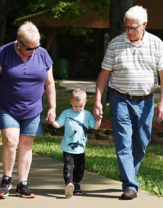 Ron and Carol Snyder took their 3-year-old grandson, Zachary Stoops, for a walk in Alameda Park Tuesday afternoon. Harold Aughton/Butler Eagle