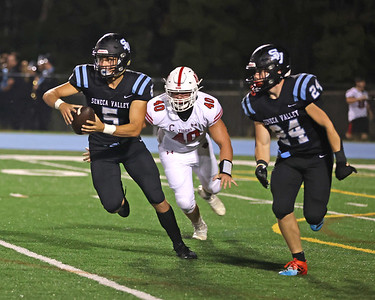 Seneca quarterback Graham Hancox scrambles away from Moon's Ben Bladel on a quarterback option that ended with a fumble on a pitch to Troy Alexander (24). Seb Foltz/Butler Eagle 08/27/21