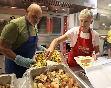 Raylene Jindra of Meridian serves up a to-go plate at Katie's Kitchen Thursday with retired Butler art teacher Jon Pugliese. Jindra has been volunteering for the kitchen since it opened in 1994. She recruited Pugliese when the two met a few years ago at a local dentist. Seb Foltz/Butler Eagle
