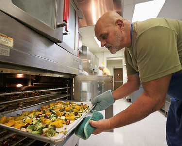 Katie's Kitchen volunteer Jon Pugliese checks on some baked vegetables Thursday, preparing to-go meals with other volunteers. Seb Foltz/Butler Eagle 09/02/21
