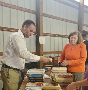 Mr. Bookman Ben Wilkinson, left, helps Penny Milanovich check out a huge stack of books at the Butler County Bookfest Friday afternoon.EDDIE TRIZZINO/BUTLER EAGLE