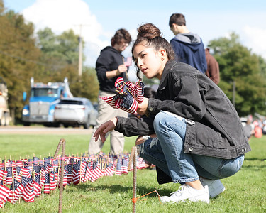 Mars JROTC junior Maddie Ostapchenko, 16, looks down the line of flags Thursday as she places flags with her fellow cadets to comemorate the victims of 9/11 at Mars High School. Seb Foltz/Butler Eagle 09/09/21
